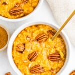 Overhead shot of two bowls of pumpkin oatmeal topped with pecans.