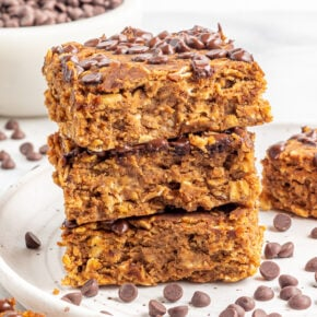 A stack of pumpkin protein bars on a white plate with chocolate chips sprinkled around.