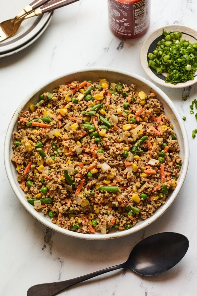 A serving bowl filled with quinoa fried rice. A black spoon rests below the bowl. Just out of frame is a bottle of sriracha and a bowl of green onions.