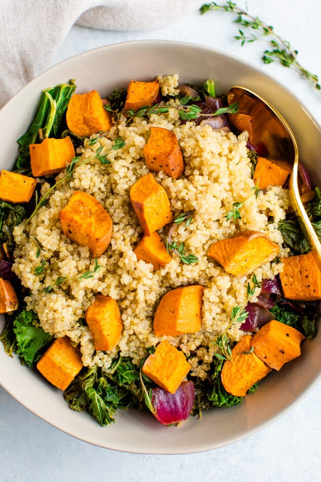 Kale salad with red onion, quinoa and roasted sweet potatoes on top.