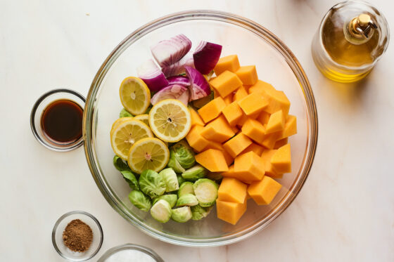 A glass bowl filled with butternut squash, onion, lemon slices, and Brussels sprouts. Additional ingredients are around the bowl.