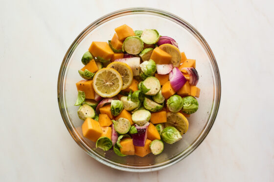Vegetables and lemon mixed together with oil and seasonings in a glass bowl.