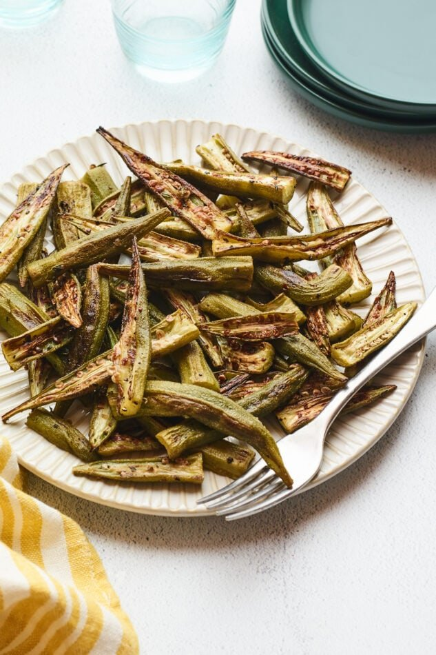 Roasted okra on a plate with a fork. A couple glasses of water and a stack of plates are beside the plate of okra.