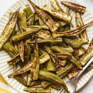 Roasted okra on a plate with a fork.