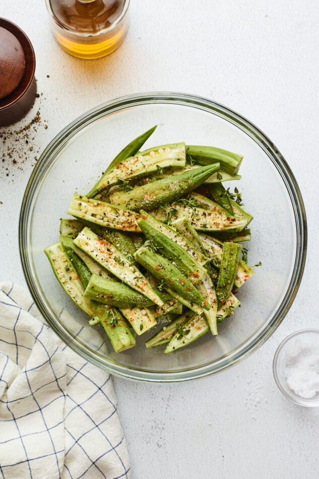 Fresh okra in a mixing bowl seasoned with spices and herbs.
