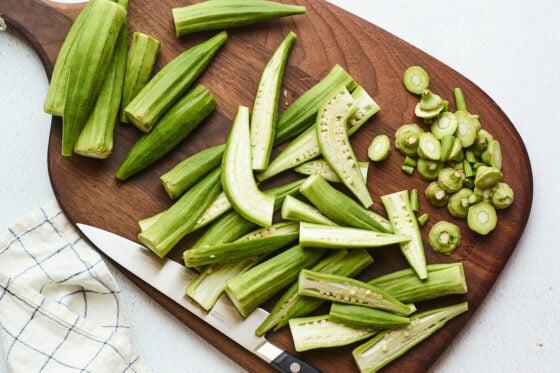 Fresh okra being chopped on a wooden cutting board.