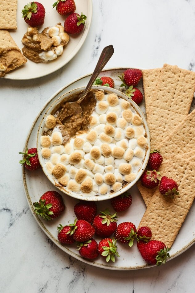 S'mores dip plated with strawberries and graham crackers for dipping. A spoon is taking a scoop from the dip.