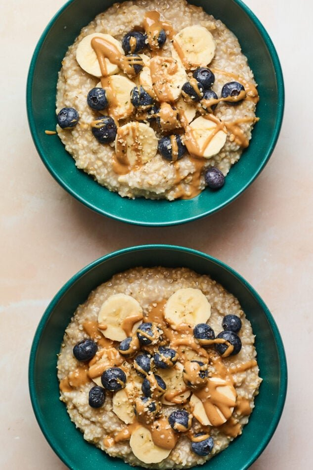 An overhead shot of two bowls of steel cut oatmeal with bananas, blueberries, and almond butter drizzled on top.