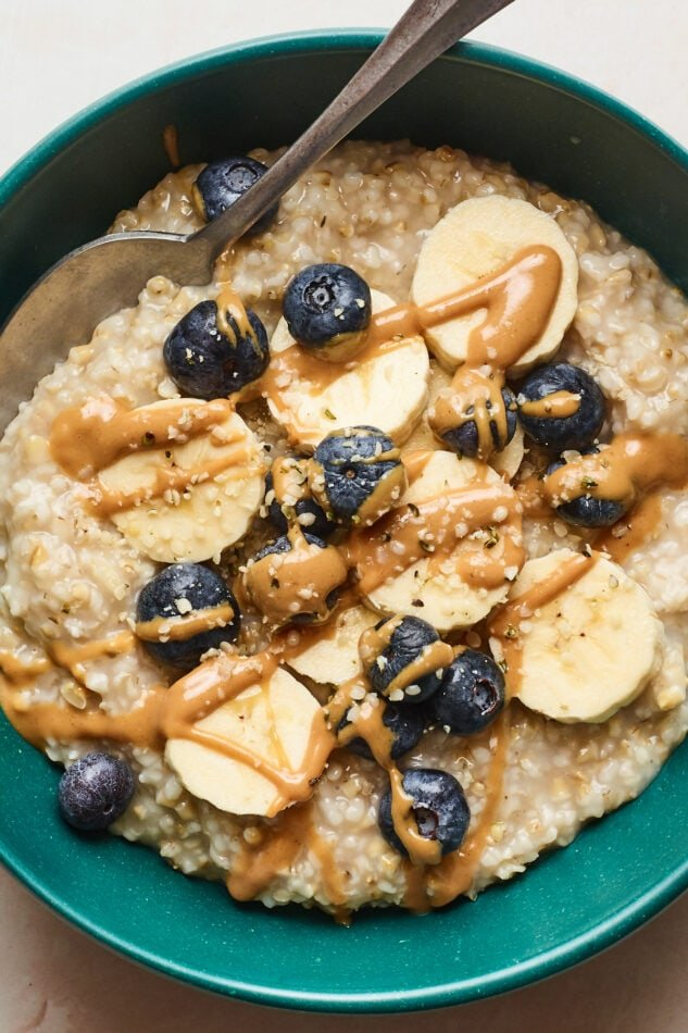 A close up shot of steel cut oats in a bowl with blueberries, bananas, and almond butter drizzled on top. A spoon rests in the bowl.