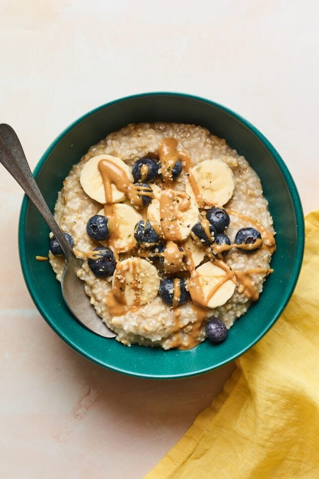An overhead shot of a bowl of steel cut oats with banana slices, blueberries, and an almond butter drizzle on top.