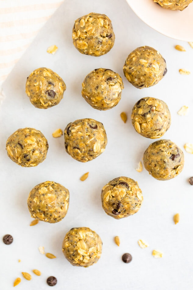 SunButter energy bites laid out on a marble surface with a few oats and chocolate chips scattered around