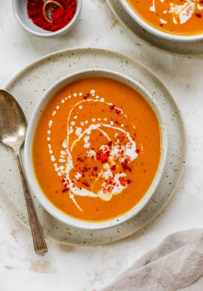 A bowl of sweet potato soup served on a plate with a metal spoon.