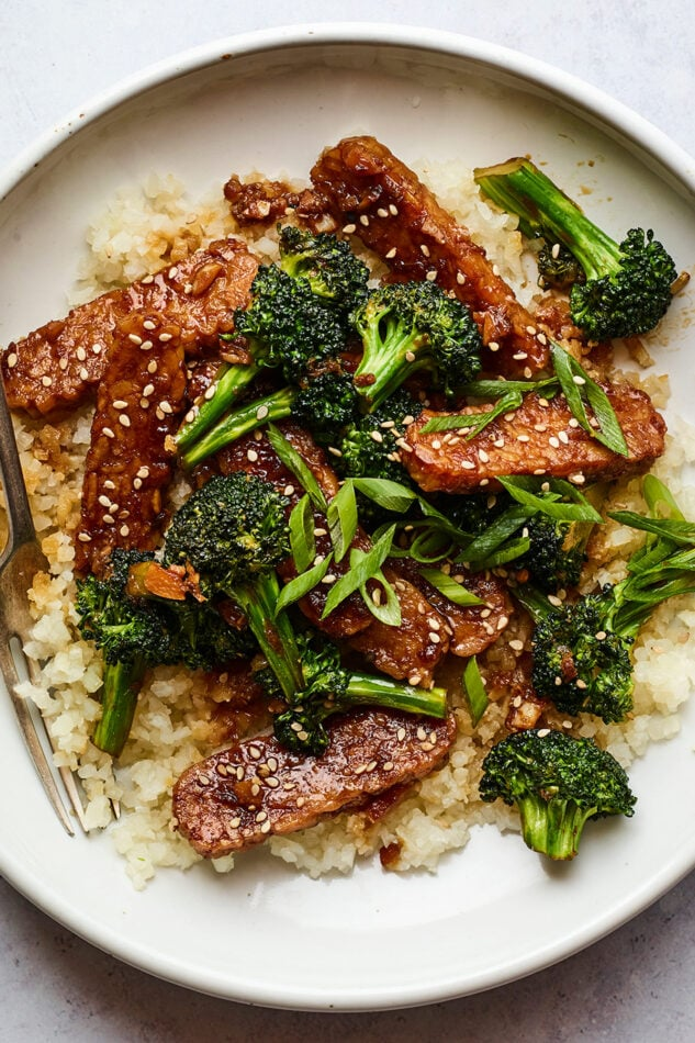 Bowl with rice topped with teriyaki tempeh and broccoli and sesame seeds. A fork is in the bowl.