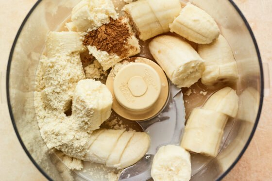 Food processor with banana, cinnamon, protein powder and peanut butter.