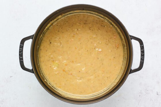 Vegan potato soup after it has been blended with an immersion blender in a cast iron dutch oven.