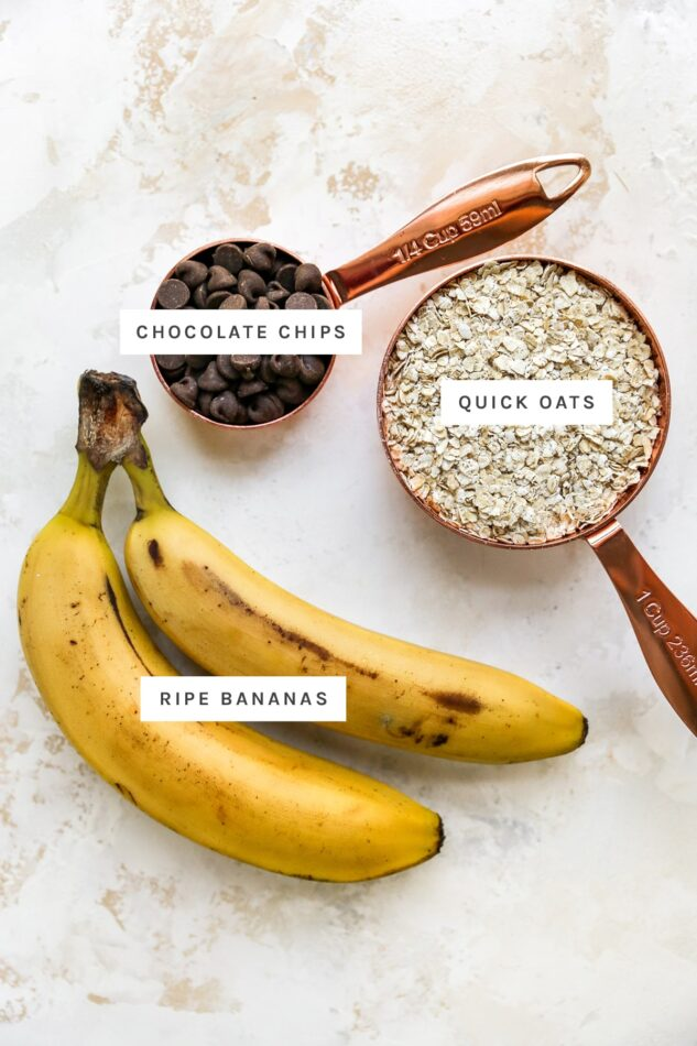 Ingredients measured out to make banana oatmeal cookies: chocolate chips, quick oats and ripe bananas.