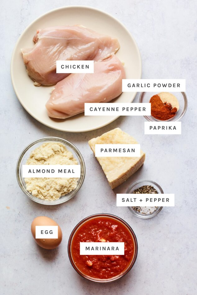 Ingredients measured out to make chicken parmesan: chicken, garlic powder, cayenne pepper, paprika, almond meal, parmesan, salt, pepper, egg and marinara.