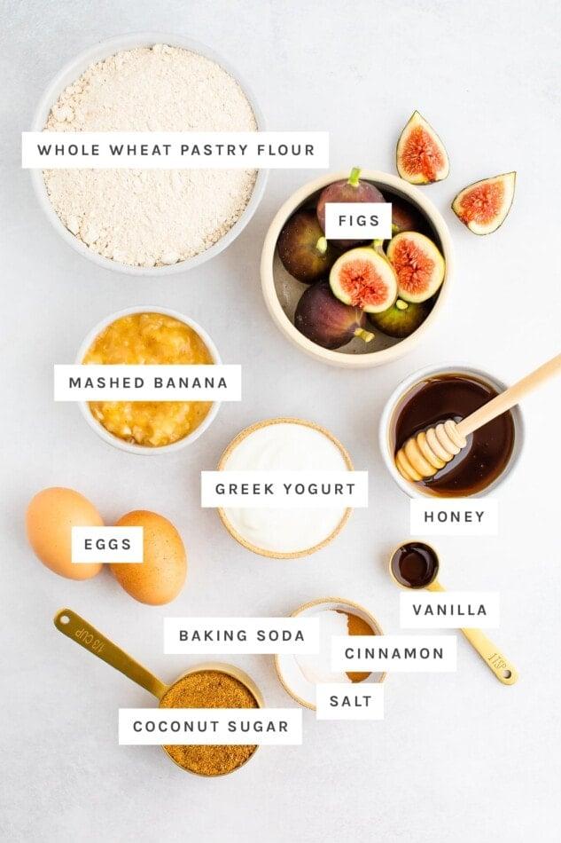 Ingredients measured out to make healthy fig bread: whole wheat pastry, figs, mashed banana, greek yogurt, honey, eggs, vanilla, baking soda, cinnamon, salt and coconut sugar.