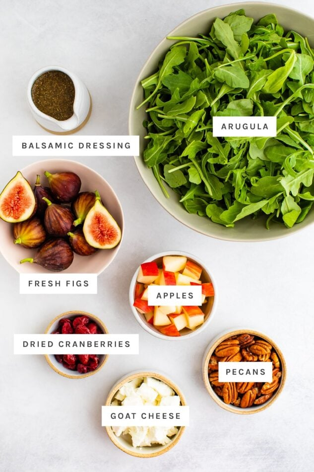 Ingredients measured out to make a fig salad: arugula, balsamic dressing, fresh figs, apples, dried cranberries, goat cheese and pecans.