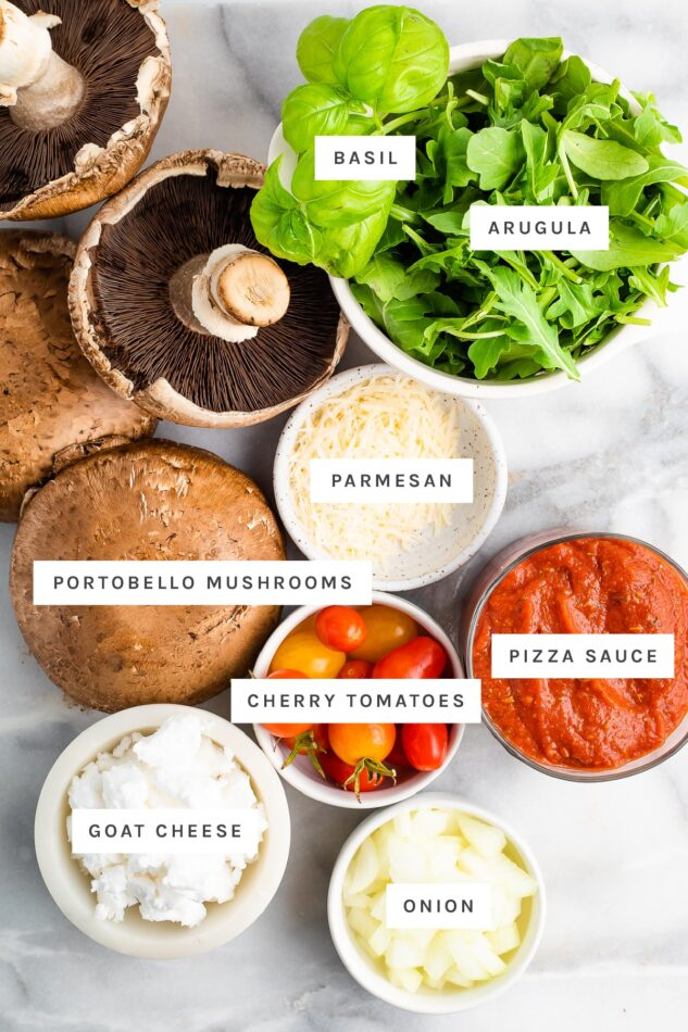 Ingredients measured out to make portobello pizzas: basil, arugula, parmesan, portobello mushrooms, pizza sauce, cheery tomatoes, goat cheese and onion.