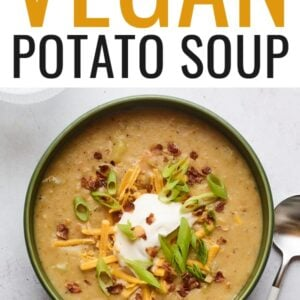 """A bowl of vegan potato soup topped with vegan sour cream, vegan shredded cheese, """"bacon"""" bits, and chopped green onions. A silver spoon rests aside the bowl."""