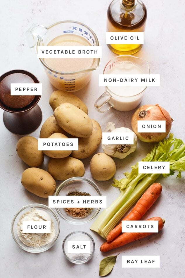 Ingredients measured out to make vegan potato soup: olive oil, veggie broth, non-dairy milk, pepper, potatoes, garlic, onion, spices, herbs, flour, celery, carrots, salt and bay leaf.