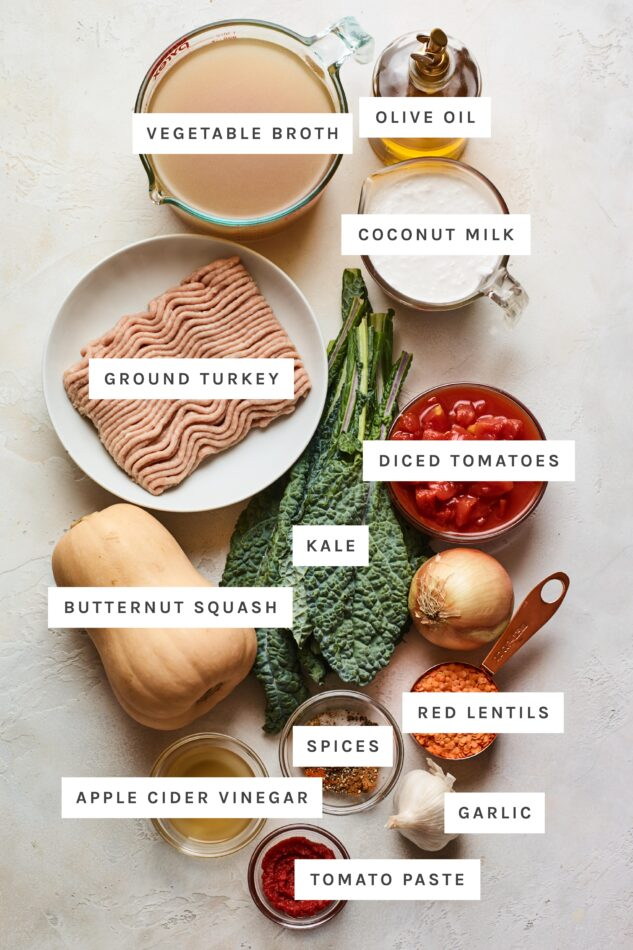 Ingredients measured out to make butternut squash turkey chili: vegetable broth, olive oil, coconut milk, ground turkey, diced tomatoes, kale, butternut squash, red lentils, spices, apple cider vinegar, garlic and tomato paste.