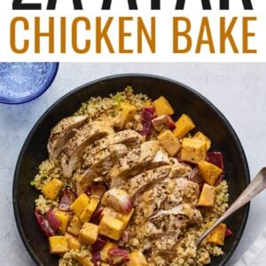 A plate of Za'atar chicken and vegetables over a bed of herbed couscous.