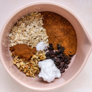 A mixing bowl with dry ingredients for a cinnamon oat filling.