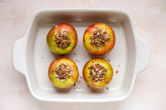 A rectangular baking dish with 4 apples filled with cinnamon oat filling.