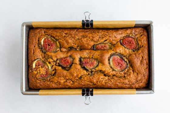 A cooked loaf of fig bread, still inside the bread baking pan.