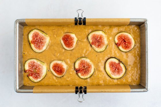 A bread pan filled with fig bread batter. 8 slices of fig are laid out on top of the bread.