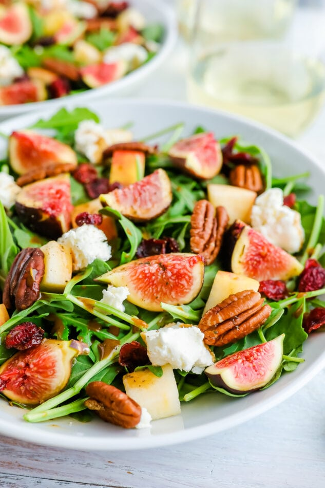 A bowl of fig salad with arugula and goat cheese. There is another bowl out of focus in the background alongside two stemless glasses of white wine.