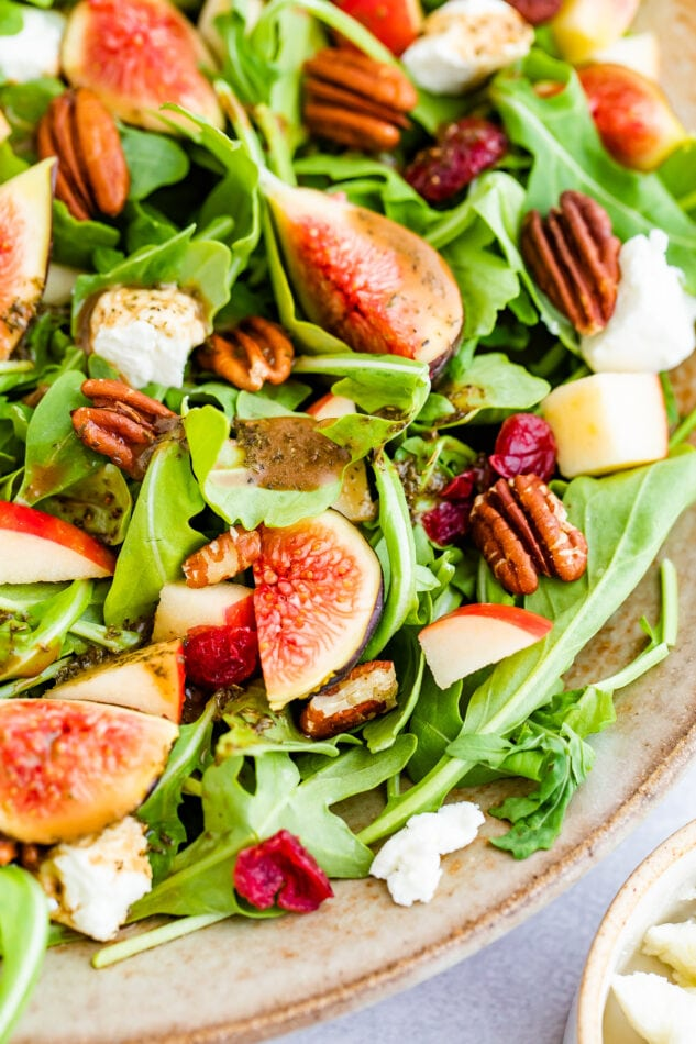 A close up of figs, pecans, apple chunks, and dried cranberry on a bed of arugula.