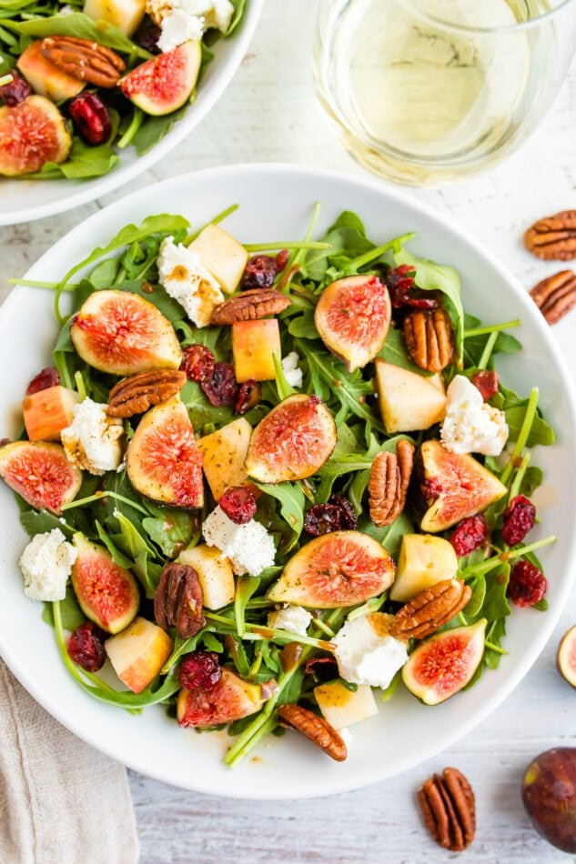 An overhead shot of a bowl of fig salad with a white wine glass next to it.