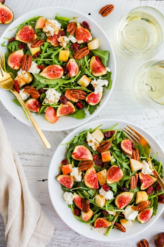 An overhead shot of two bowls of fig salad next to two glasses of white wine. A gold fork rests inside each bowl.