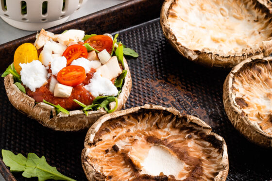 A portobello mushroom cap on a sheet pan, topped with arugula, pizza sauce, goat cheese, and sliced cherry tomatoes. Additional ingredients surround the sheet pan and there is another portobello mushroom cap with no toppings on the sheet pan.