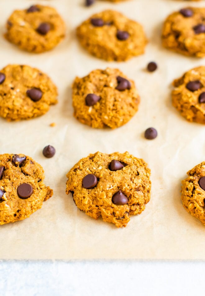 A piece of parchment paper with 9 cookies neatly in rows. There are extra chocolate chips sprinkled around the cookies.