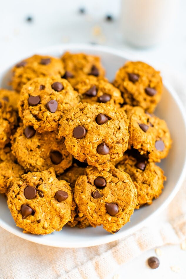 A white bowl filled with pumpkin oatmeal cookies.