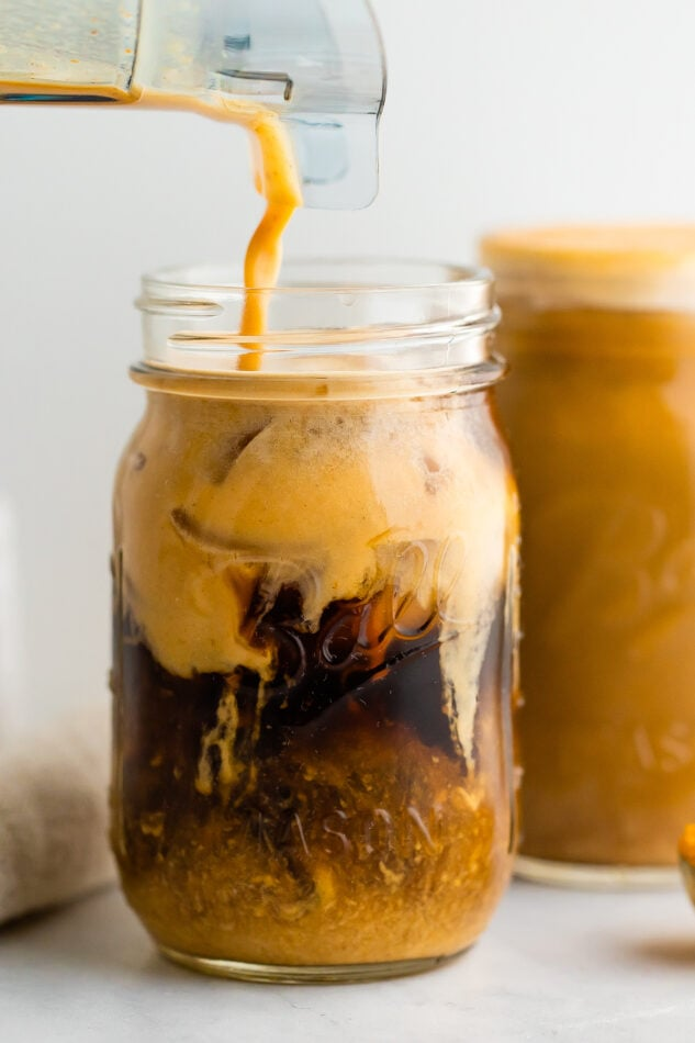 A mason jar with cold brew coffee and pumpkin cream being poured in. The cream is mixing in with the cold brew.