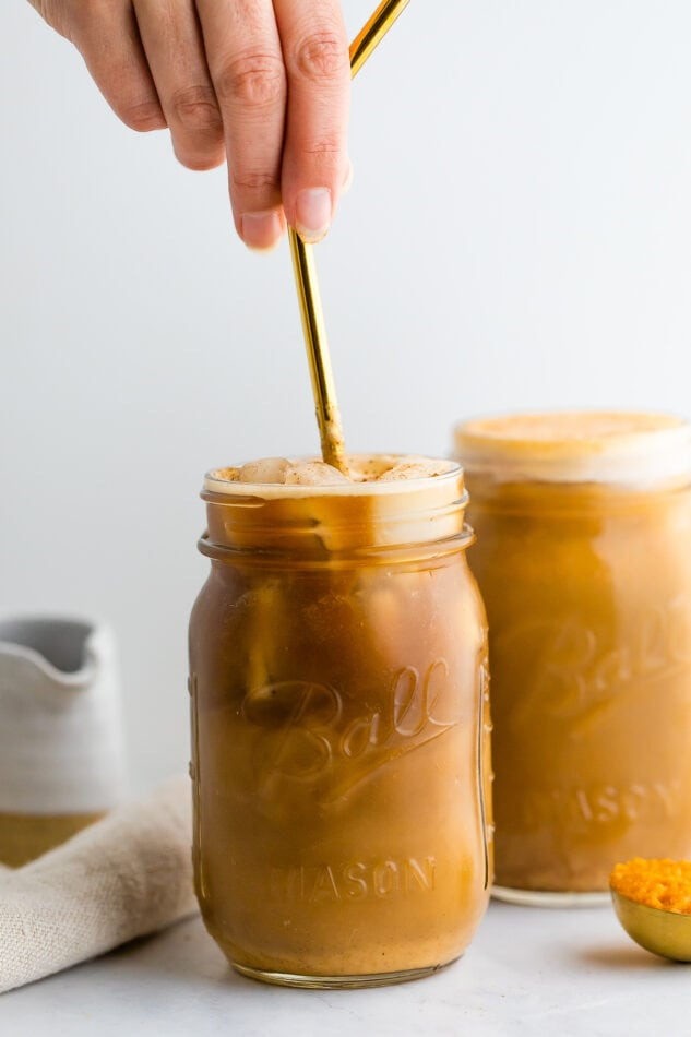 A hand is using a gold metal straw to mix pumpkin cream into cold brew in a mason jar. A full mason jar with pumpkin cream cold brew is in the background.