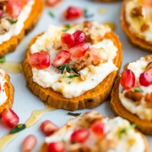 A sweet potato bite topped with pomegranate arils, pecans and fresh thyme is in focus, surrounded by other bites that are not in focus.