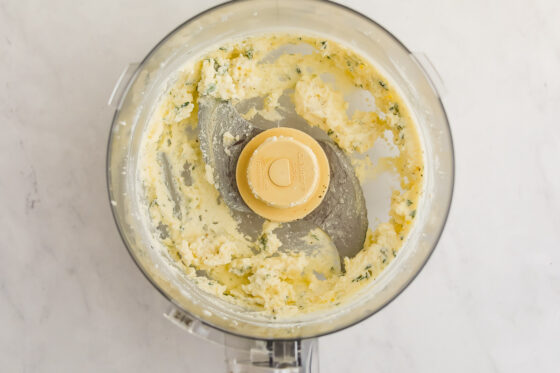 A food processor with freshly whipped ricotta and fresh thyme.