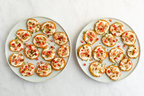 Two identical plates holding sweet potato rounds with whipped ricotta, pomegranate arils, pecans and fresh thyme sprinkled on top.