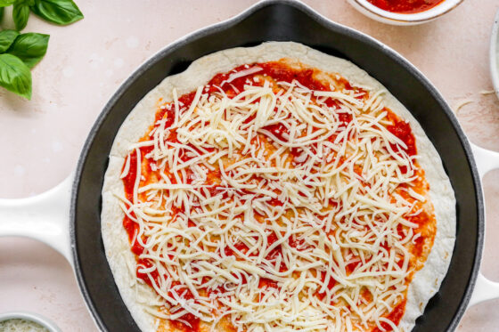 Cheese sprinkled onto of pizza sauce on a tortilla in a skillet.