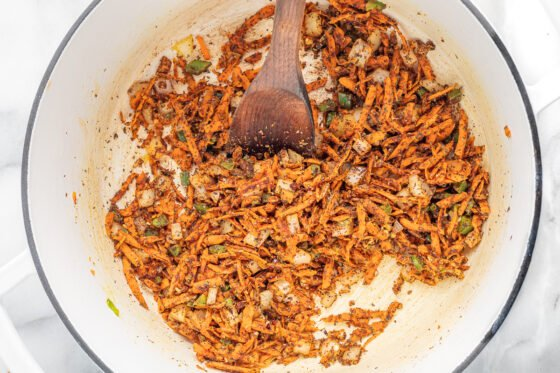 Seasonings were added and mixed into the shredded carrots and vegetables. A wooden spoon rests in the pot.