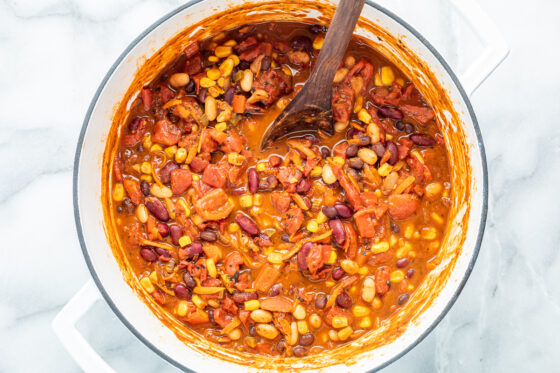 Ingredients for vegetarian chili mixed together in a pot with a wooden spoon.