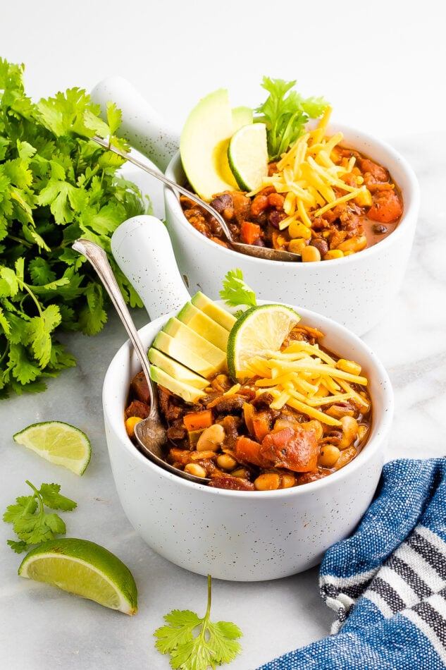 Two bowls of chili topped with avocado, lime wedge, and shredded cheese. A bunch of cilantro and some lime wedges are scattered around the bowls.