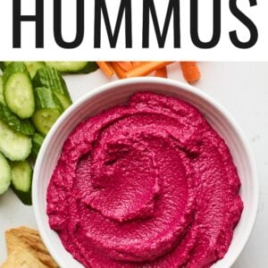 Overhead photo of a bowl of beet hummus surrounded by various veggies for dipping.