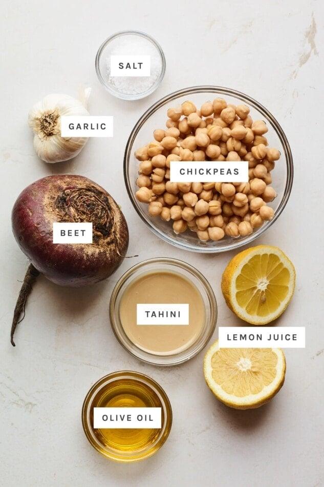 Ingredients measured out to make beet hummus: salt, garlic, chickpeas, beet, tahini, lemon and olive oil.